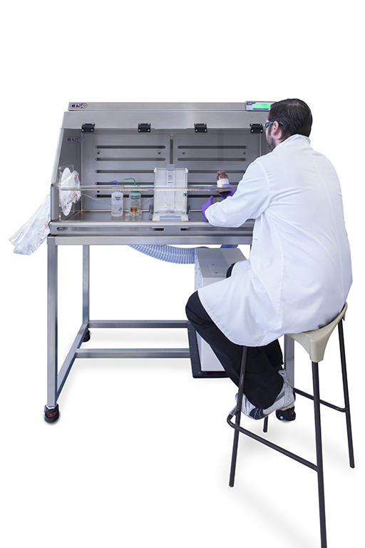 Analysist handling chemicals inside the enclosure with measuring equipment
