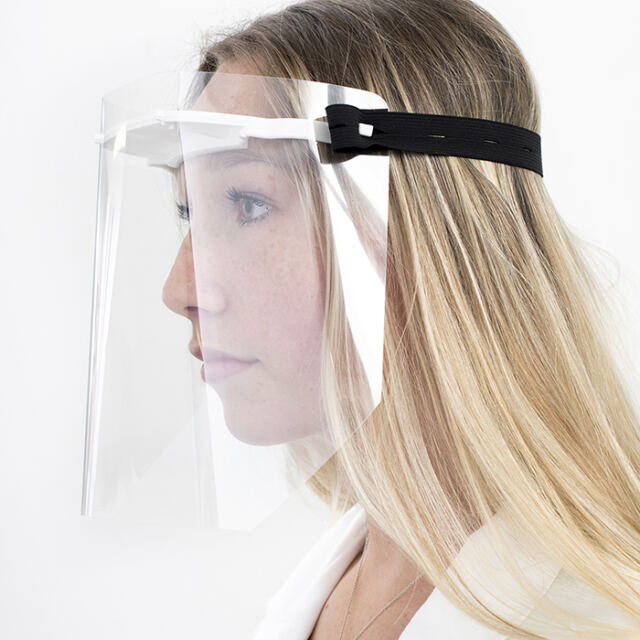 Side view of young scientist wearing a face shield over goggles