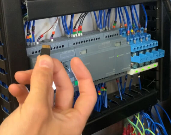 engineer holding a mini SD card before inserting into a Logo controller