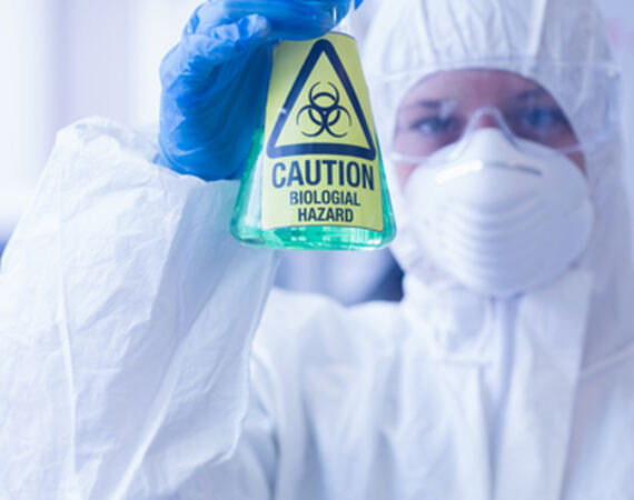 Laboratory analyst holding a biohazard in a bottle with a green liquid